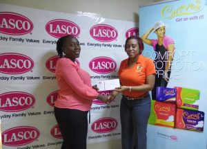 Cloverlyn Earle (Left) smiles as she is handed a cheque of $20,000 for winning in the Win Your Wings with Curves promotion. Renee Rose, Brand Manager at LASCO presents her the cheque.